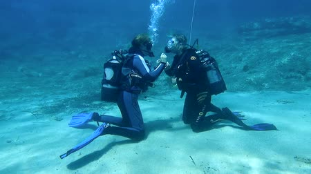 mergulhador : HALKIDIKI,GREECE- JULY 19 2014:Scuba diving instructor teaching her student to dive.