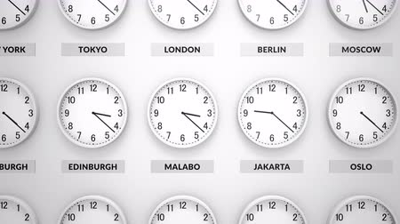 отходы : Round clocks with white body show different time zones on White wall. Camera moves left to right. Clock face timelapse 60fps animation Стоковые видеозаписи