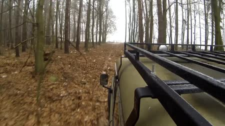 Riding the car off-road through thet forest at winter time - footage from carrier