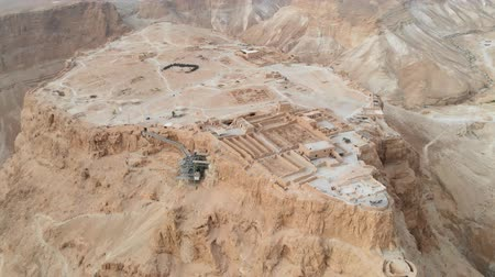 Soaring aerial 4K view MASADA, ISRAEL. Filmed flying drone. flying around Masada, an ancient Jewish fortress in the Israeli desert. Israeli soldiers on top of the mountain. 動画素材