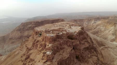 israelite : Masada fortress area Southern District of Israel Dead Sea area Southern District of Israel. Ancient Jewish fortress of Roman Empire on top of a rock in the Judean desert. front view from the air 4k