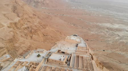 historical reconstruction : Masada fortress area Southern District of Israel Dead Sea area Southern District of Israel. Ancient Jewish fortress of the Roman Empire on top of a rock in the Judean desert. front view from the air Stock Footage