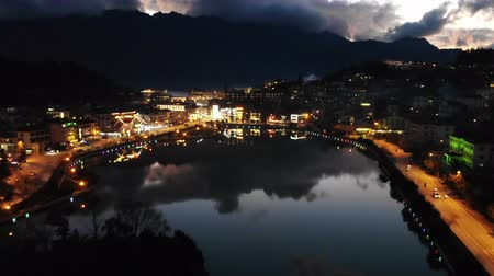 cai : Night city landscape view with mountain background and cloudy sky reflection on water located at SAPA, Vietnam. Lake in the center of Sapa. motion, move fly