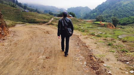 visa : young guy walks along the road among the rice terraces in the village of cat kat near the city of Sapa. Vietnam.