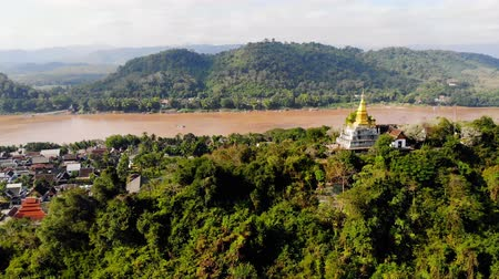 luang : Panorama view of Luang Prabang Laos. top Phou Si, the hill that dominates city, popular location for sunrise sunset views. golden stupa on the top of Mount Phou Si Stock Footage
