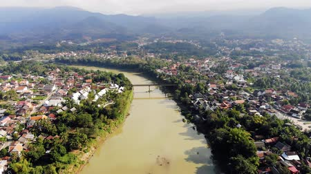 prabang : Aerial view of Luang Prabang and surrounding lush mountains of Laos. Nam Kahn River, a tributary of the Mekong River, flows peacefully on the right. Stock Footage