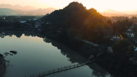 khan : Luang Prabang, Laos. Aerial view Luang Prabang town in Laos. Cloudy sky over small city surrounded by mountains. Mekong river Stock Footage