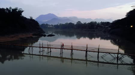 luang : young Girl tourist walks on the bridge of bamboo across the river in Luang Prabang. Laos. 4K move drone Stock Footage