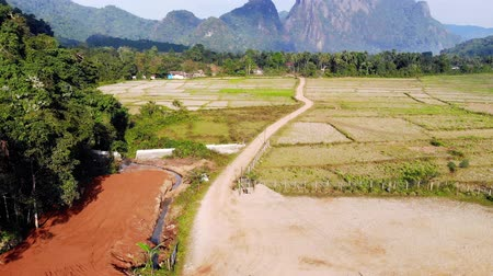 economia rural : Blue lagoon, Vang vieng, Laos. flying over rice fields on the background of high mountains and hills