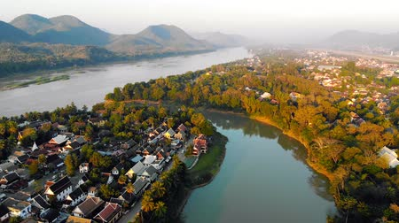 luang : Aerial view of Luang Prabang and surrounding lush mountains of Laos. Nam Kahn River, a tributary of the Mekong River, flows peacefully on the right. Stock Footage
