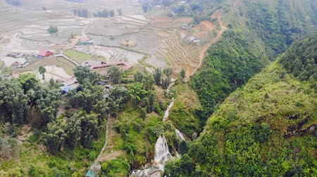hilltribe : Aerial view of green terraced rice fields and building on the valley at Cat Cat village in Sapa, 4K move flying drone Stock Footage