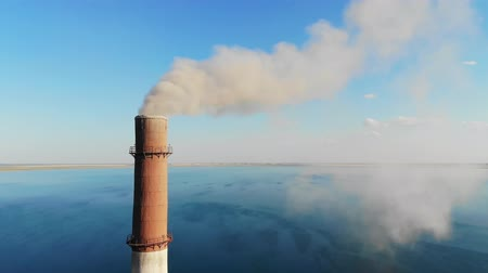 bad ecology : Gray smoke comes out of a large brick chimney in the factory against a clear blue sky and a large lake. 4K video. Environmental pollution. bad ecology, modern problems. smog