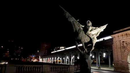 oszlopsor : Metro Traffic on Bir-Hakeim bridge (Passy) at night with France Reborn Statue (La France renaissante) in foreground - Paris, France