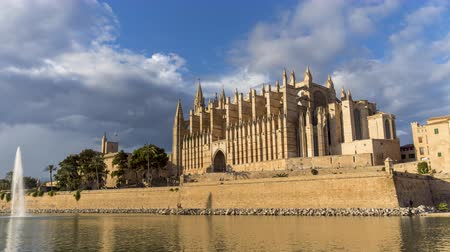 baleár : 4k Timelapse of la Seu, the Cathedral of Palma de Mallorca, and Royal Palace of La Almudaina at sunset with clouds - Balearic Islands. Stock mozgókép