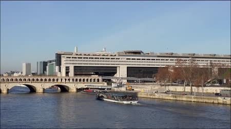 french metro : Boats traffic under Bercy bridge with French Ministry for the Economy and Finance in background - Paris, France