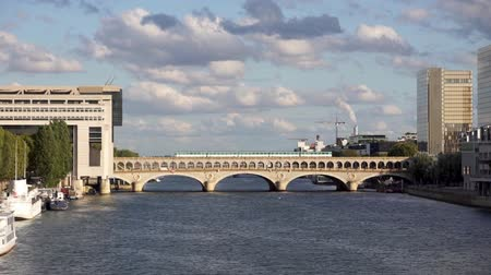 french metro : Metro crossing Bercy bridge with French Ministry for the Economy and Finance and National Library of France in background - Paris, France