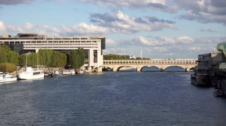 french metro : Metro crossing Bercy bridge with French Ministry for the Economy and Finance in background - Paris, France