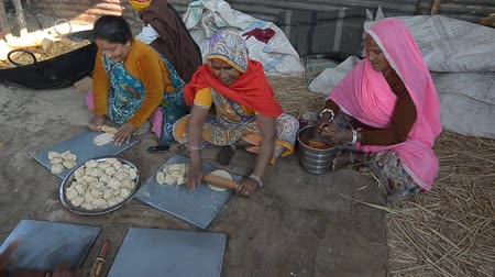 ALLAHABAD,INDIA-CIRCA,FEBRUARY 2013:Women prepare the bread in the days of  Kumbh Mela.The largest gathering of people on the history in Allahabad, India February 2013.