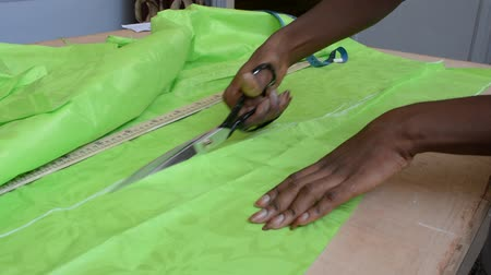 tailor cuts the cloth with the scissors