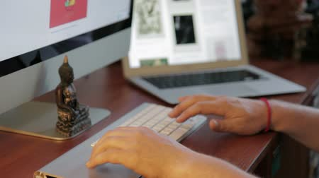 website : Side view with depth and perspective blur of designer working at a wooden desk. Wire framing and web design happening on a computer in the distance while designer focuses on another monitor. Part of my hipster designer working at office or agency series. Stock Footage