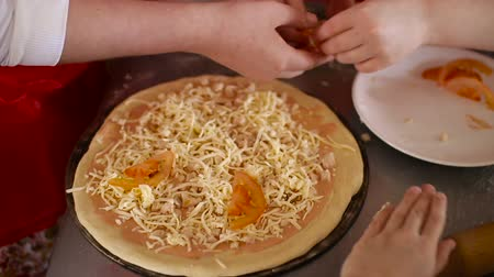 хлеб : Putting cheese topping on pizza dough already coated with tomato sauce