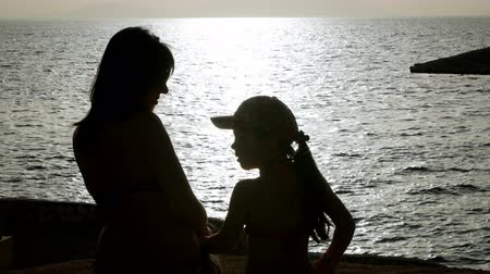 mother love : beautiful mother and daughter meet the sunrise at the sea Stock Footage