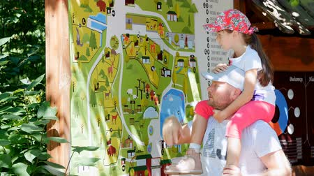 szándékozik : father and daughter are studying the map of the zoo