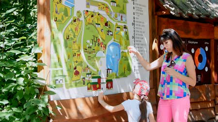szándékozik : mother and daughter are studying the map of the zoo