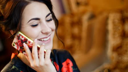 falar : beautiful girl talking on the phone in a dressing gown at home.