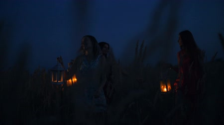 noční prádlo : Beautiful girls walking in the field - in the hands holding candle lanterns.