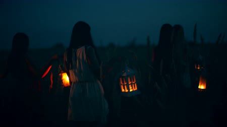 atividades : Beautiful girls walking in the field - in the hands holding candle lanterns.