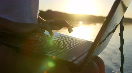 latino americana : yacht girl working at a laptop - sun glare in the water.