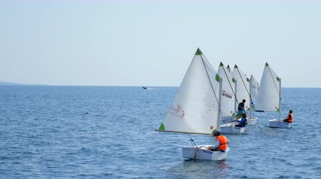 żaglowiec : On the sea small sailing training boats with children sail. Children learn to manage sailboats, yachts, boats. A clear summer day, a calm Mediterranean sea, a marina in Athens Wideo