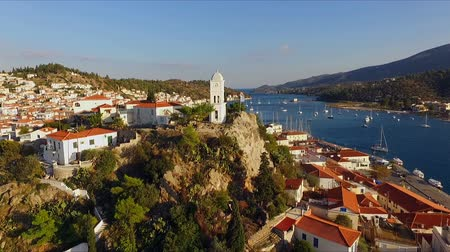 saronic : landscape Greek island of Poros amidst the Mediterranean, with a birds-eye view, aerial video shooting, many moored to the pier, sailing yachts, catamarans, the strait between the islands, a landscape of mountains, sea, blue sky, white buildings with red