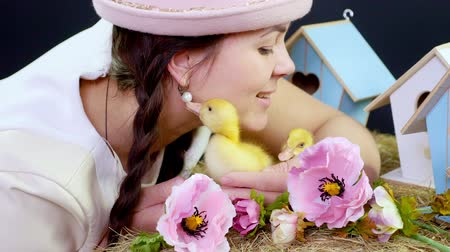orphans : Portrait, a pretty young woman with two pigtails and in a funny pink hat playing with small yellow ducklings. Studio video with thematic decor.