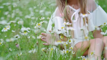 sadece kadınlar : portrait. Blonde girl, child, sits in the grass, among the daisies, in the chamomile meadow. She admires the daisies. Her hair is decorated with a wreath of daisies. She smiles,