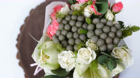 single headed : Top view, close-up of a bouquet of flowers, rotation , consists of eucalyptus, cineraria, Rose cream grace, Rose barbados, Eustoma, solidago, Santini , feverweed, Brunia green.