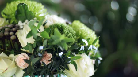 single headed : close-up, Flower bouquet in the rays of light, rotation, the floral composition consists of Brunia green, Rose of avalanche, Rose yana creamy, Santini , gypsophila, eucalyptus