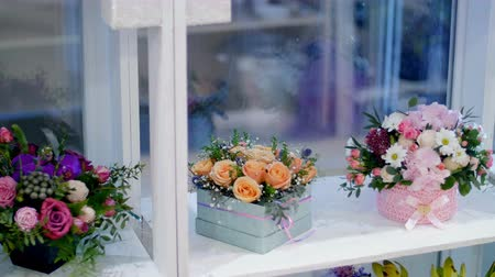 roomy : Flower shop, on the show-window, there are a lot of bouquets of flowers , floral stylish compositions in colorful boxes with different flowers