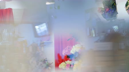поощрение : Through the showcase of a flower shop, you can see many different flowers and bouquets. the entire flower shop-studio reflects In the glass of window. The depth of space is felt.