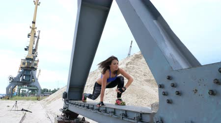 zihinsel : athletic woman in a Blue top and striped leggens performs strength exercises.She stands on the metal beam of a freight crane. fitness at dawn, on the beach in a cargo port.