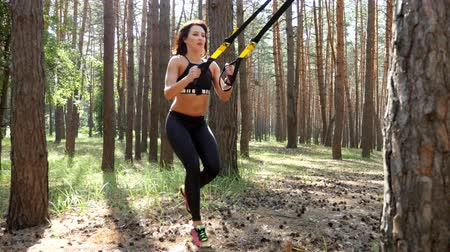 Beautiful, athletic, sexy young woman, coach, instructor, performs exercises, doing exercises with fitness trx system, TRX suspension straps. In pine forest, in summer, in sun rays.