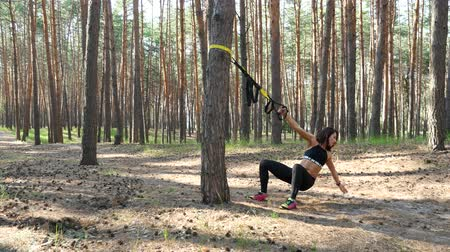 levantamento de pesos : Beautiful, athletic, sexy young woman, coach, instructor, performs exercises, doing exercises with fitness trx system, TRX suspension straps. In pine forest, in summer, in sun rays.