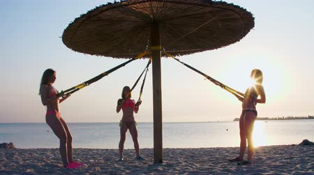 eğitici : three athletic, sexy young women in swimsuits, instructors, doing exercises with fitness trx system, TRX suspension straps. On the beach, in summer, at sunset, in sun rays.
