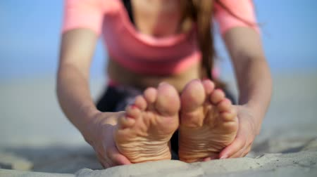 çim : Beautiful blond woman doing stretching exercises on the beach. Close-up of foot