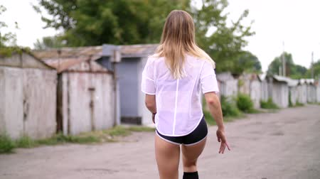 hatalmas : sexy athletic young blond woman in shorts, performs various strength exercises with the help of tires, jumps. In summer, near old abandoned garages Stock mozgókép