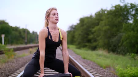 lift ups : Beautiful sexy athletic young blond woman in black leggings performing exercises with a heavy weight plate, On the railway, on rails, sleepers, in the summer. Slow motion