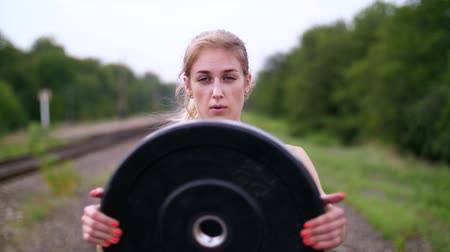lift ups : Beautiful sexy athletic young blond woman in black leggings performing exercises with a heavy weight plate, On the railway, on rails, in the summer. Slow motion. portrait