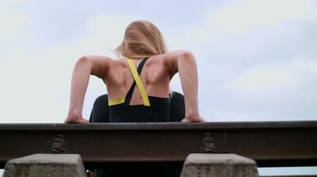 lift ups : Beautiful sexy athletic young blond woman in black leggings performing exercises to make strong arm muscles, presses on hands. Sits on sleepers, on a railway, in summer, rear view