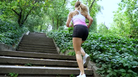 lift ups : Beautiful sexy athletic young blond woman in a T-shirt and shorts, runs upstairs, in the forest, park, in summer day. Bottom view, from the back. Slow motion Stock Footage